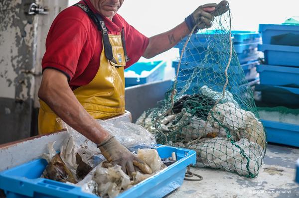 Un pêcheur triant le plastique pêché